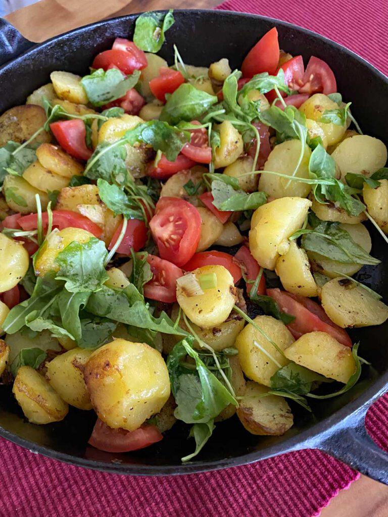 Rustikale Kartoffelpfanne mit Tomaten und Rucola